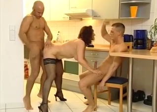 Brunette blows her two hung sons in the kitchen